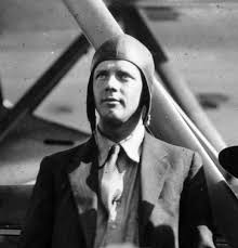 Charles Lindbergh standing by his airplane the Spirit of St. Louis.