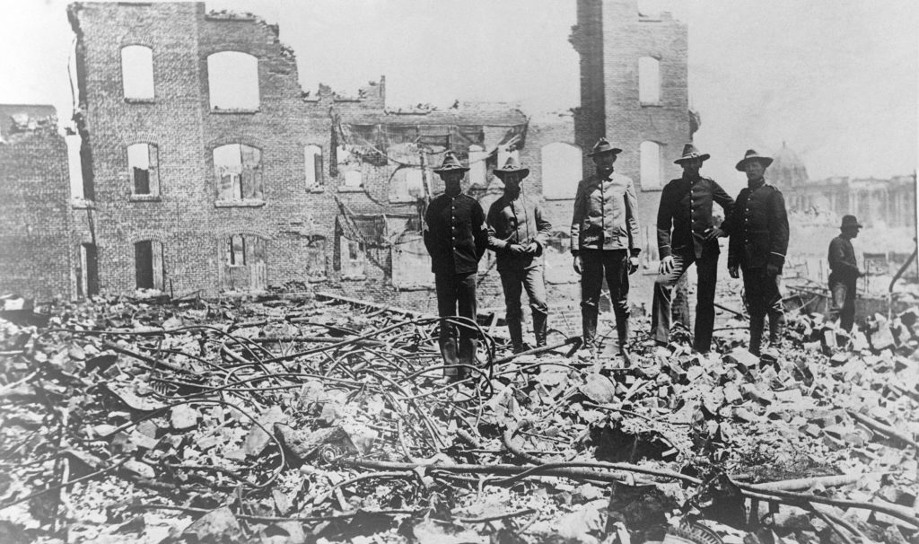 Soldiers from the Presidio stand amid the rubble of fallen buildings after the earthquake. The Hall of Records (dome) is in the background (right). 1906